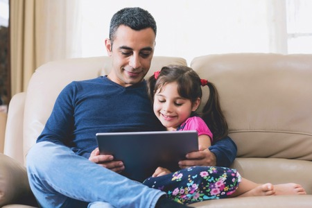 Little Girl And Father Looking At Digital Tablet Screen Together Stock Photo