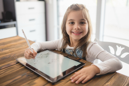 Little Girl Drawing Digital Picture On Electronic Touch Pad With Stylus Pen