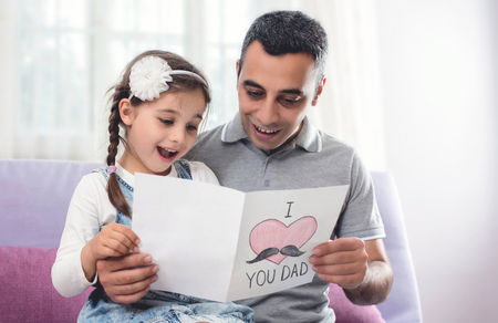 Happy Fathers Day Portrait. Child daughter and Her Daddy are Hugging and Reading the Surprise Postcard Together. Stock Photo