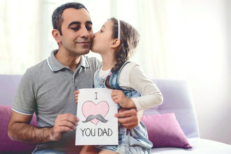 Happy Fathers Day Portrait. Child Daughter Kissing Her Smiling Dad and Congratulating Him with a Postcard.