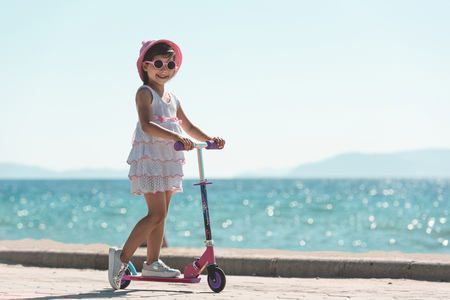 Happy Child Girl Tourist Riding Scooter At Seaside in Summer