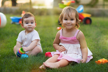 Happy Smiling Baby Brother and Toddler Sister Playing with Toys Togerther in Backyard Garden in Summer Season at Sunset Stock Photo