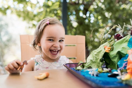 Happy Smiling Baby Girl Playing Game With Toys Outdoors in Summer