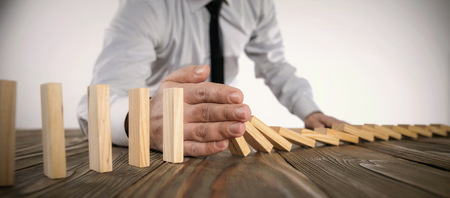 Chain Reaction In Business Concept, Businessman Intervening Dominoes Toppling Stock Photo