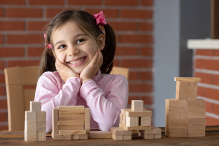 Happy Smiling Child Girl Playing With Wooden Toys At Home Banco de Imagens