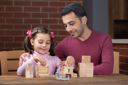 Happy Smiling Child Girl and Father Playing With Wooden Toys At Home