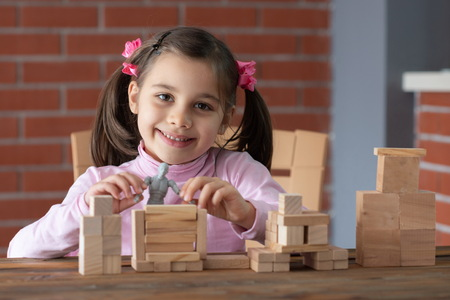 Happy Smiling Child Girl Playing With Wooden Toys At Home Stock Photo