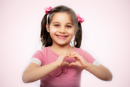 Close Up Portrait Of A Sweet Child Girl With Shallow Depth Of Field Doing Heart Gesture, On Pink Background