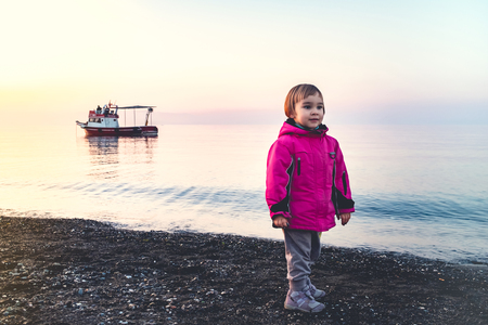 Little Child Girl Playing with Stones at Seaside in a Spring Season Evening, with Sunset light
