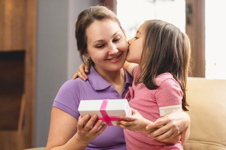 Happy Mothers Day Celebrating Concept. Child Daughter Giving Present to Her Mom. Stock Photo