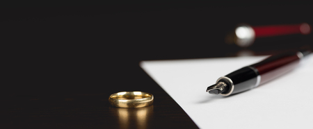 Signing or Writing Divorce Document Concept on Table with Dark Background