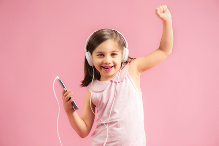 Child Girl Listening To Music and Dancing on Pink Background