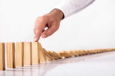 Chain Reaction In Business Concept, Businessman Letting Or Preventing  Dominoes Continuous Toppling On Rustic Wooden Desk