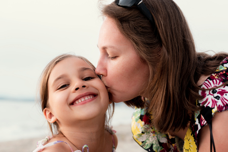 Portrait Of Happy Mother and Daughter Outdoors at Beach in Summer Season