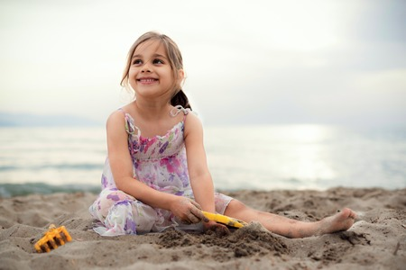 Happy Child Girl Playing with Sand at Beach in a Summer Evening