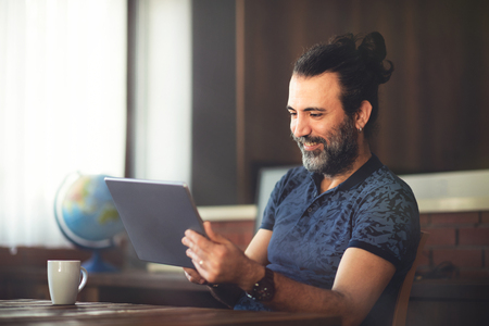 New Successful Smiling Entrepreneur Hipster Businessman Working in Office with Digital Tablet Stock Photo