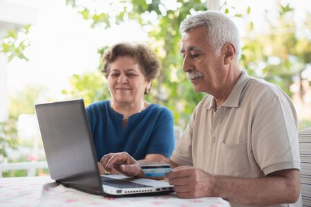 Happy Senior Couple Doing Online Shopping Using Credit Card Outdoors in Garden or in Cafe Stock Photo