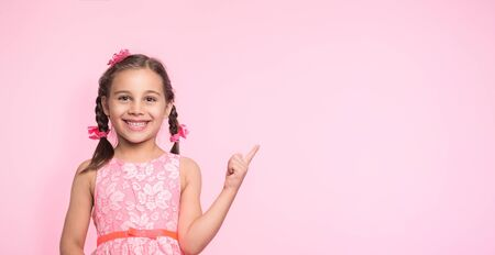 Portrait Of Child Girl Gesturing on Pink Background with Available Copy Space