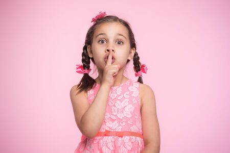 Portrait of Child Girl Gesturing to Say Silence, on Pink Background