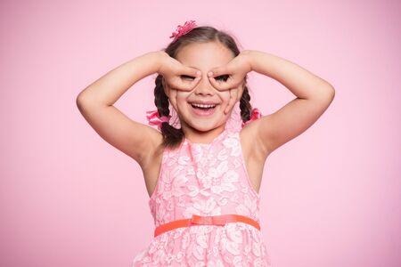Portrait of Child Girl Gesturing  on Pink Background