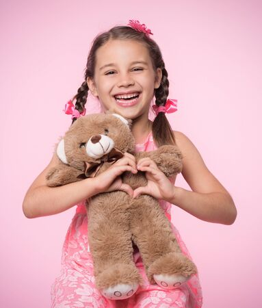 Portrait of Child Girl Hugging Her Soft Toy Bear on Pink Background and Doing Heart Gesture