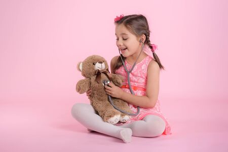 Happy Child Girl Doctor Examining Her Dear Toy Bear on Pink Background Banco de Imagens