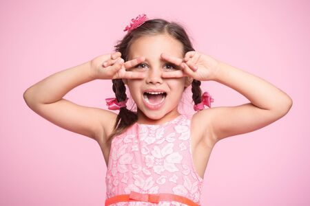 Portrait of Child Girl Gesturing  on Pink Background