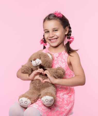 Portrait of Child Girl Hugging Her Soft Toy Bear on Pink Background and Doing Heart Gesture Stock Photo - 127242460