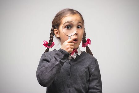 Child Girl Student Looking Through Magnifying Glass on Grey Background with Available Copy Space. Back to School Concept. 写真素材