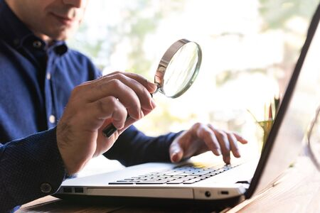 Man Holding a Magfifying Glass Searching On Internet Stock Photo - 133316516