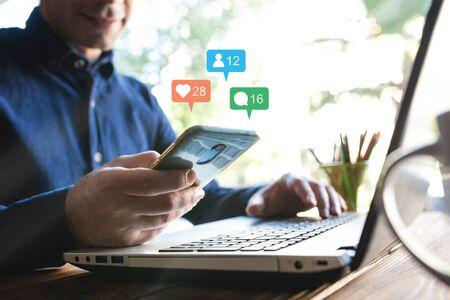 Man Checking His Social Media Account Using Smart Phone Stock Photo - 132541421