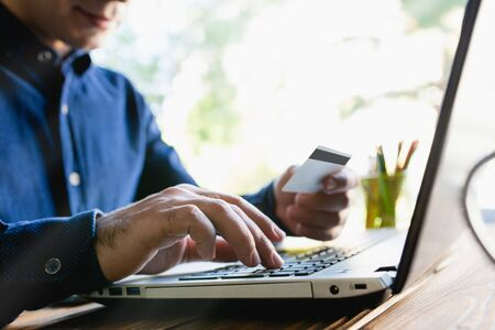 Male Hands Shopping On Laptop With Credit Card On Rustic Wooden Table In Office Stock Photo - 132870492