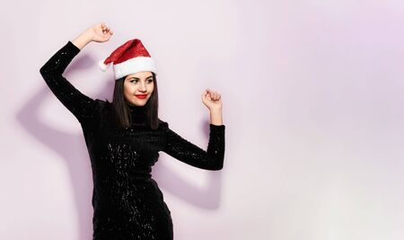 Beautiful Brunette in Black with Christmas Celebration Hat Stock Photo - 133562219