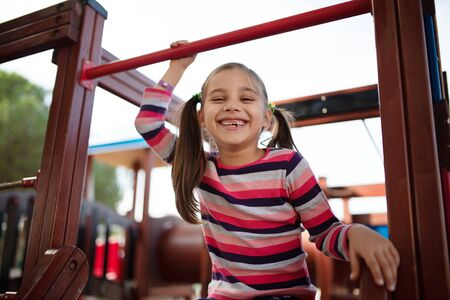 Happy Smiling Child Girl Playing At Playground Outdoors In Park Stock Photo - 135461009