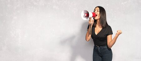Beautiful Brunette Woman Shouting Through Megaphone. Communication and Advertising Concept. Stock Photo - 135461010
