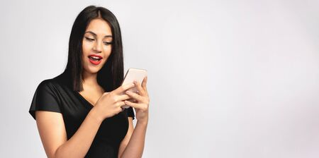Brunette Woman Using Her Smartphone with Excited Expression, Social Media Concept Stock Photo - 137337983