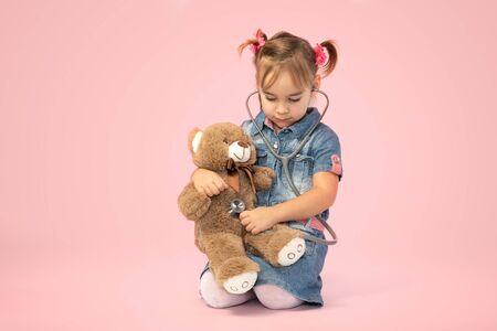 Happy Child Girl Doctor Examining Her Dear Toy Bear on Pink Background Stock Photo - 137337990