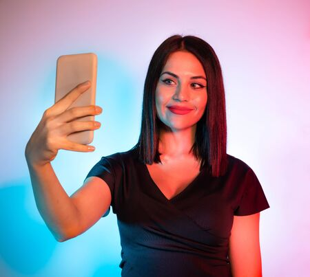Woman taking Self Portrait Photo, Selfie Concept, Studio Shot Stock Photo - 137337986