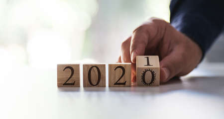 Businessman flipping over block for 2020 to 2021. Business, new year and Covid-19 Concept.