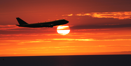 vliegtuig vliegt over de zee bij zonsondergang