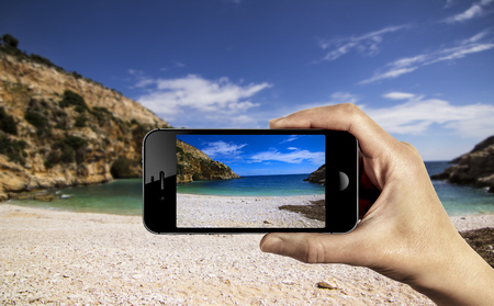 take photo with cellphone on the beach