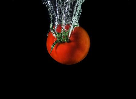 splash tomaat geïsoleerd zwarte hebben Stockfoto