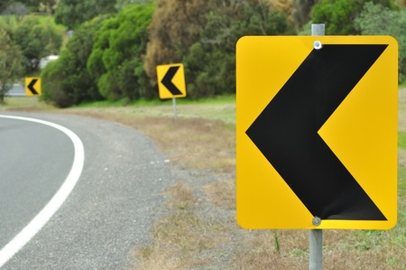 road conditions: Three turn road sign on curveed road  Stock Photo