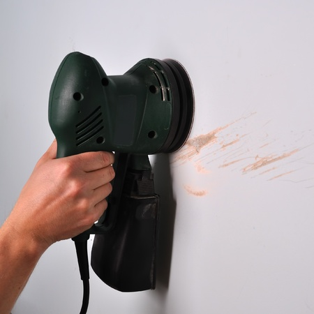 sander: Sanding scratches on damaged wall with electric round sander Stock Photo