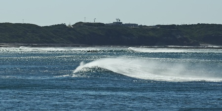 swell: Big paddle boat in rough conditions with strong offshore wind and large swell in Western Port, Victoria, Australia