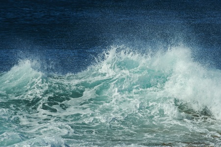rough sea: Close-up to broken wave with spray, rough surface, foam and blue ocean in background