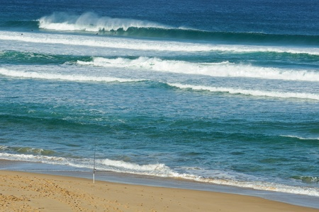 Swell and fishing rod set up at sandy beach while large waves breaks with spray and surfers diving under wave in Mornington Peninsula, Victoria, Australia Stock Photo - 13211480