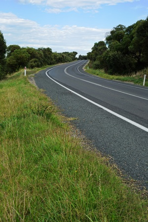 Green grass on the edge of curving road with dark asphalt and white marking line winding through forest, blue sky and small clouds in background photo
