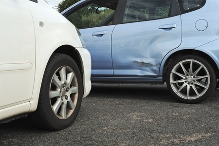 Blue and white cars stopped in light accident so door of blue car is bent, the paint is scratched and needs repair