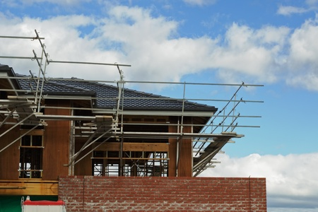 scaffolds: Secondary store of constructed house in scaffolds, wooden frame, roof tiles, brick wall and blue sky with clouds